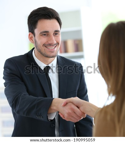 Woman giving handshake to financial adviser - stock photo