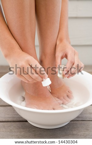 Woman giving herself pedicure - stock photo