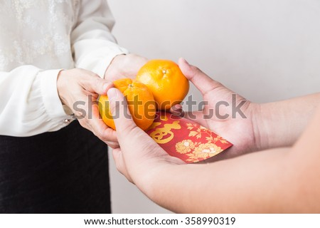 Woman giving mandarin oranges and red envelop with Good Luck character, a tradition during Chinese New Year - stock photo
