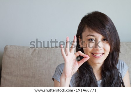 woman giving ok hand sign, asian caucasian mixed race - stock photo