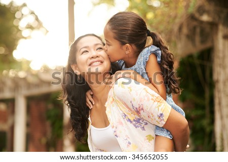 Woman giving piggyback ride to her daughter - stock photo