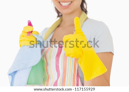 Woman giving thumbs up in rubber gloves holding cleaning products - stock photo