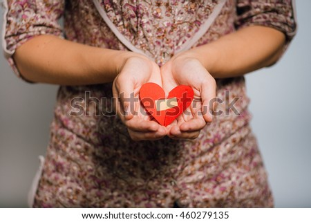 woman glued broken heart on the background