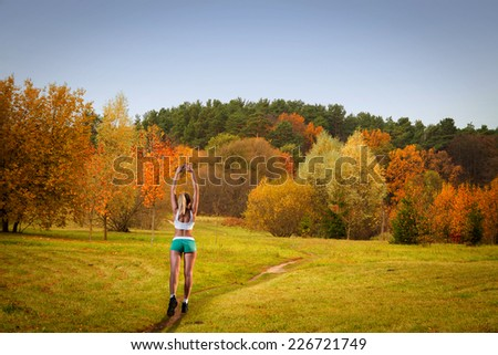 woman goes in for sports. Walks through Europe. golden autumn on the lake. everything was yellow in the fall. - stock photo