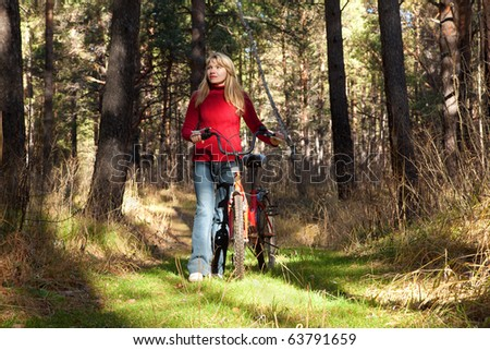 woman goes on forest with bicycle
