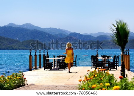 woman goes to a restaurant on the pier - stock photo