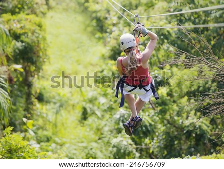 Woman going on a jungle zipline adventure - stock photo