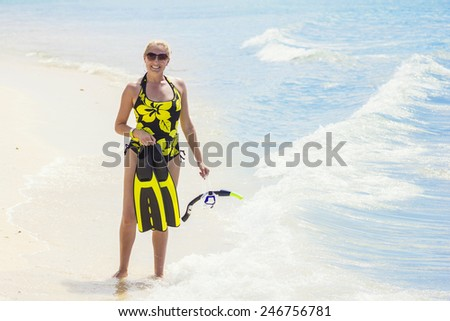 Woman going snorkeling while on a tropical vacation - stock photo