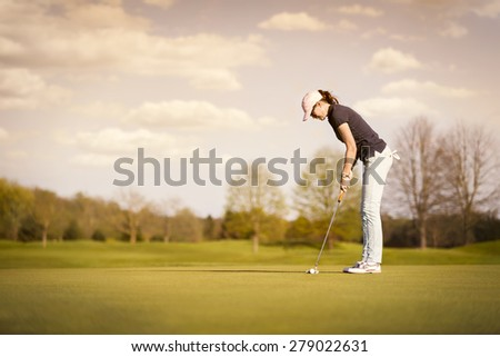 Woman golf player putting on green at dusk, with empty copyspace. - stock photo