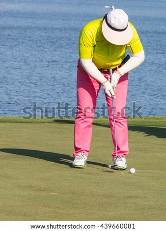 Woman golf player putting on green with lake in background. Thailand.  Golf player woman putting ball into hole on green field over beautiful summer day background. play golf. golf course. golf sport. - stock photo