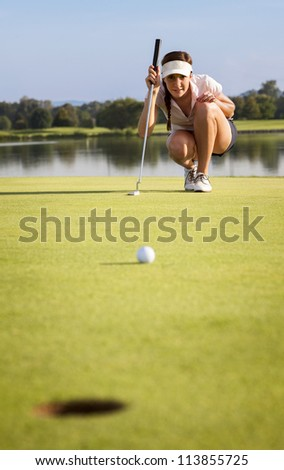 Woman golf player squatting to analyze the green for putting the golf ball into the hole. - stock photo