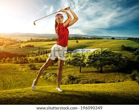 Woman golfer hitting the ball on the background scenery  beautiful - stock photo