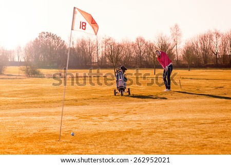 Woman golfer playing a round of golf in late evening sunlight lining up on the fairway for a shot with her golf cart in the foreground and long shadows cast by the sun - stock photo