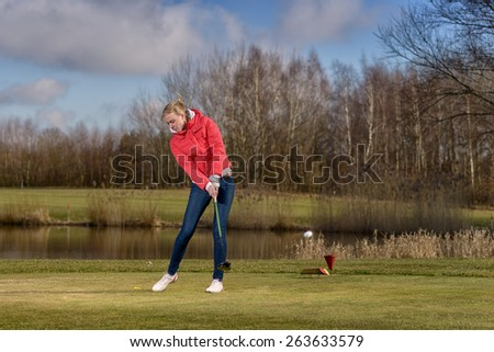 Woman golfer striking the golf ball with her club as she follows through on her stroke with the ball midair in front of her as she enjoys a round of golf on the course - stock photo