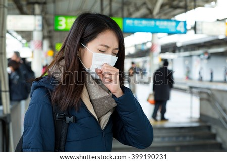 Woman got sick and wearing face mask at train station - stock photo