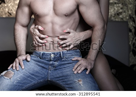 Woman grasps sexy macho mans abs at night - stock photo