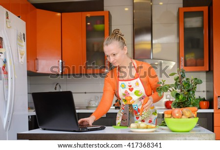 Woman grate carrots in the kitchen, with notebook.  - stock photo