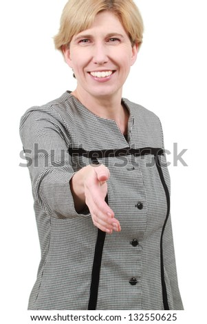 Woman greeting a visitor with a smile and a handshake - stock photo