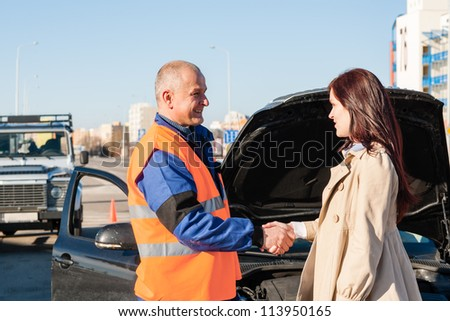 Woman greeting mechanic after her car breakdown problem man technician - stock photo