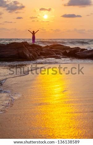 Woman greets sun the sea shore during sunrise - stock photo