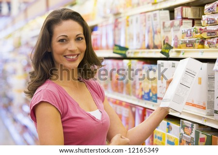 Woman grocery shopping in supermarket - stock photo
