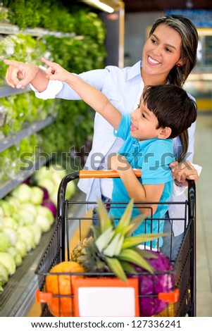 Woman grocery shopping with her kid at the supermarket