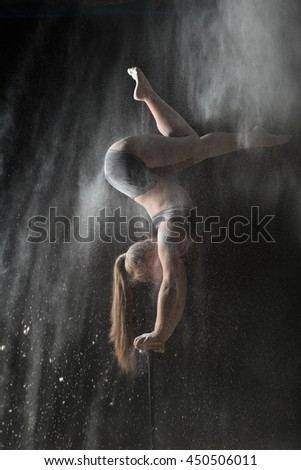 Woman gymnast handstand on equilibr while sprinkled flour - stock photo