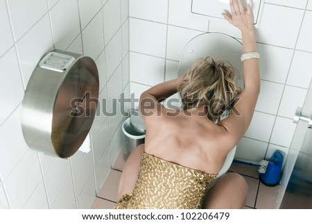 Woman had too many drinks and is drunk and is throwing up in the toilet - stock photo