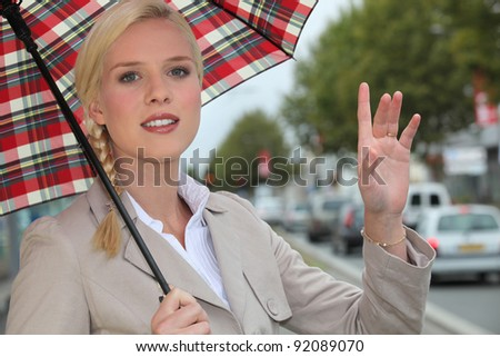 Woman hailing a taxi - stock photo