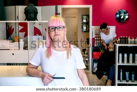 Woman hairdresser standing in hair and beauty salon - stock photo