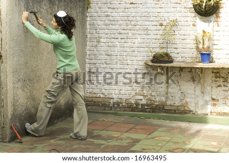 Woman hammers nail into wall. She is wearing a dust mask on her head. Horizontally framed photo. - stock photo