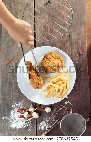Woman Hand and fried chicken wings with french fries on wood table. - stock photo