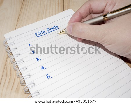 Woman hand are writing 2016 Goals in notebook on wood background (Business Concept)