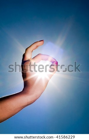 Woman hand around the sun and blue sky