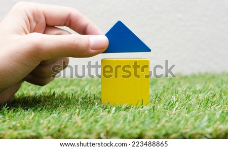 Woman hand building a small house with colorful wooden blocks - stock photo