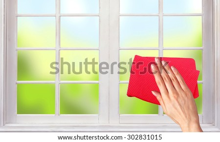 Woman hand cleaning the window - stock photo
