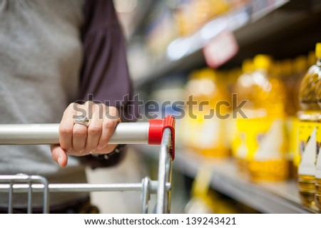 Woman hand close up with shopping cart in a supermarket walking trough the aisle. - stock photo