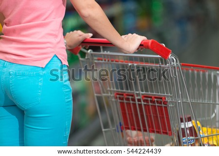 Woman Hand Close Up With Shopping Cart in a Supermarket Walking Trough the Aisle