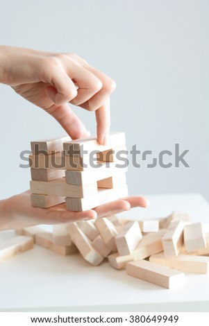 Woman hand constructing a tower of wooden blocks on a white background - stock photo