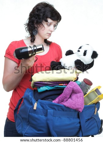 woman hand crammed full of clothes in black and blue shoulder bag isolated on white