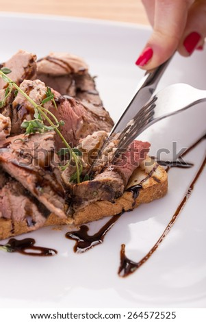 Woman hand cutting roast beef sandwich with lettuce and liver paste on wooden background - stock photo