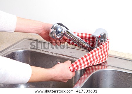 Woman hand doing chores in the kitchen at home , cleaning sink and faucet