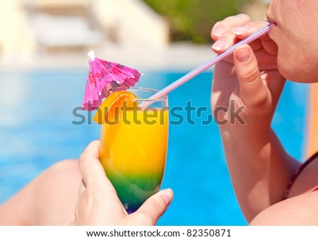 Woman hand drinking cocktail with plastic straw near swimming pool