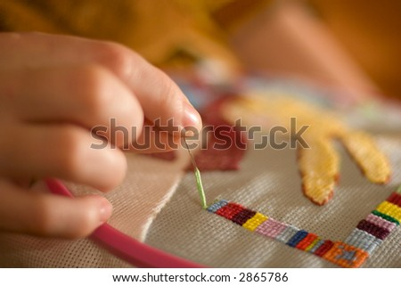woman hand embroiders with a needle and a thread - stock photo