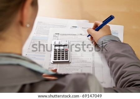 Woman hand filling income tax forms with calculator - stock photo