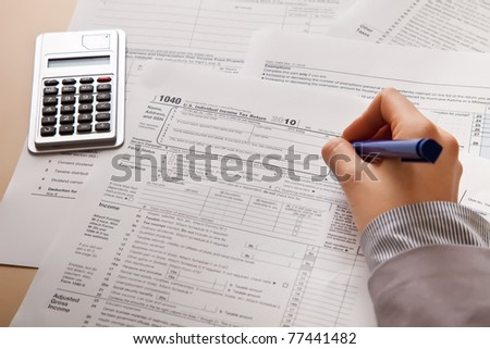 Woman hand filling income tax forms with calculator