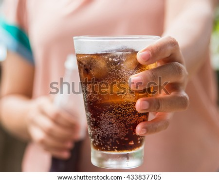 Woman hand giving glass of cola.Glass of cola ,Soft drinks with ice. - stock photo