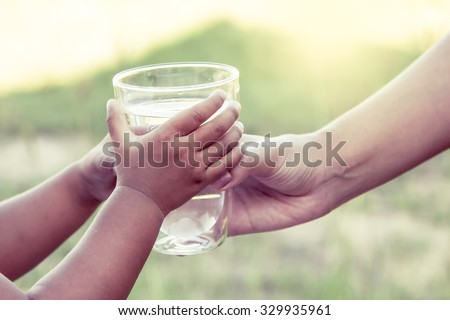 Woman hand giving glass of fresh water to child in the park,vintage color filter - stock photo