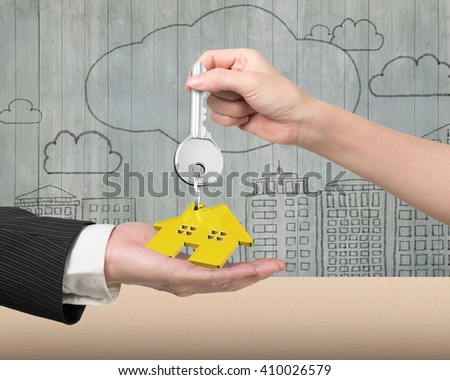 Woman hand giving silver key with gold house shape keyring to man hand, on doodles wooden wall background. - stock photo