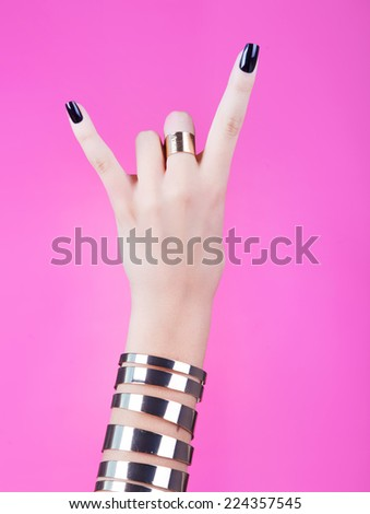 Woman hand giving the devil horns gesture  - stock photo